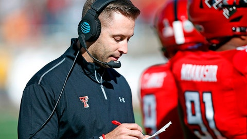 FILE - In this Nov. 18, 2017, file photo, Texas Tech coach Kliff Kingsbury looks down at his notes during the second half of the NCAA college football game TCU, in Lubbock, Texas. Kingsbury is still popular at Texas Tech, five years after his hiring as coach unified a fractured football program at his alma mater. (AP Photo/Brad Tollefson, File)