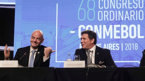 FIFA President Gianni Infantino, left, talks with Alejandro Dominguez, right, president of the South American Football Confederation, CONMEBOL, during their annual conference in Buenos Aires, Argentina, Thursday, April 12, 2018. CONMEBOL has asked FIFA to expand the World Cup to 48 teams for the 2022 tournament in Qatar. (AP Photo/Martin Ruggiero)