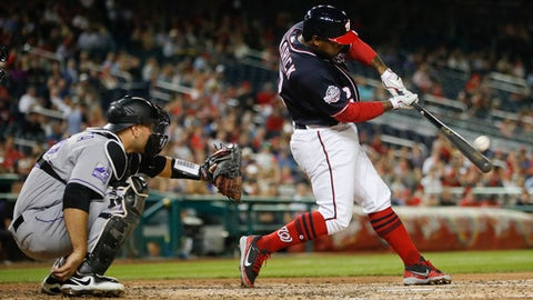 Washington Nationals' Howie Kendrick (12) connects for a solo homer off Colorado Rockies starting pitcher Chad Bettis during the fifth inning of a baseball game at Nationals Park, Thursday, April 12, 2018, in Washington. Behind the plate is Rockies catcher Chris Iannetta. (AP Photo/Pablo Martinez Monsivais)