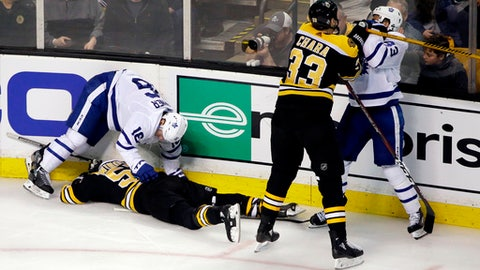 FILE - In this April 12, 2018, file photo, Boston Bruins defenseman Zdeno Chara (33) shoves Toronto Maple Leafs center Nazem Kadri (43) to retaliate for his late hit on Boston Bruins center Tommy Wingels (57), bottom left,  as Maple Leafs center Mitchell Marner (16) starts to get up during the third period of Game 1 of an NHL hockey first-round playoff series, in Boston. Through the first two days of the Stanley Cup playoffs, there have already been a handful of hits to the head, two ejections, one suspension and the possibility of more to come. (AP Photo/Elise Amendola)