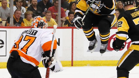 Pittsburgh Penguins' Sidney Crosby (87) leaps out of the way of a shot from the point against Philadelphia Flyers goaltender Brian Elliott, left, during the second period in Game 2 of an NHL first-round hockey playoff series in Pittsburgh, Friday, April 13, 2018. (AP Photo/Gene J. Puskar)