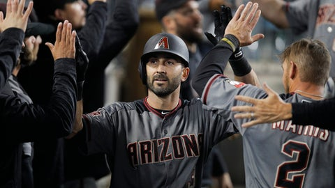 Arizona Diamondbacks' Daniel Descalso, center, is congratulated in the dugout for his two-run home run during the seventh inning of the team's baseball game against the Los Angeles Dodgers, Friday, April 13, 2018, in Los Angeles. (AP Photo/Jae C. Hong)