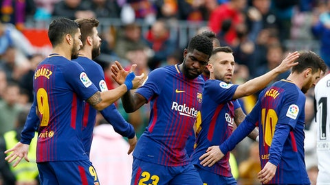 FC Barcelona's Samuel Umtiti, center, celebrates with teammates after scoring during the Spanish La Liga soccer match between FC Barcelona and Valencia at the Camp Nou stadium in Barcelona, Spain, Saturday, April 14, 2018. (AP Photo/Manu Fernandez)