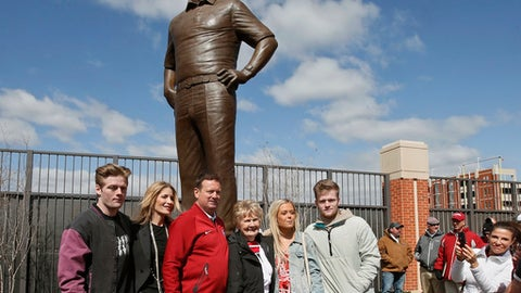 Former Oklahoma head coach Bob Stoops, center, poses with his family, from left, son Drake, wife Carol, mother Dee, daughter Mackenzie and son Isaac,  in front of his statue, following it's unveiling at the Gaylord Family Memorial Stadium before the annual NCAA college football spring intra-squad game in Norman, Okla., Saturday, April 14, 2018. (AP Photo/Sue Ogrocki)