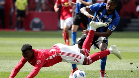 New York Red Bulls midfielder Derrick Etienne, bottom, is tripped up by Montreal Impact defender Chris Duvall during the second half of an MLS soccer match, Saturday, April 14, 2018, in Harrison, N.J. The Red Bulls won 3-1. (AP Photo/Julio Cortez)