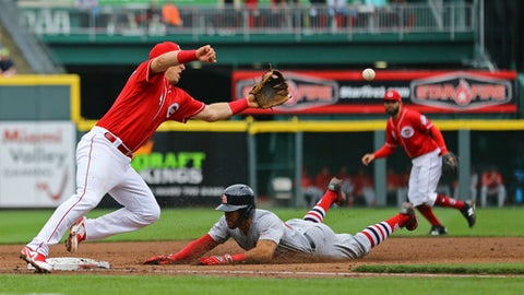 St. Louis Cardinals' Tommy Pham steals third base ahead of the throw to Cincinnati Reds' Cliff Pennington in the fifth inning of a baseball game, Saturday, April 14, 2018, in Cincinnati. (AP Photo/Aaron Doster)