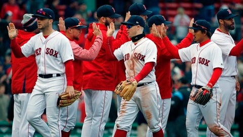 Boston Red Sox players, from left foreground, Andrew Benintendi, Brock Holt and Tzu-Wei Lin celebrate after defeating the Baltimore Orioles in a baseball game in Boston, Saturday, April 14, 2018. (AP Photo/Michael Dwyer)