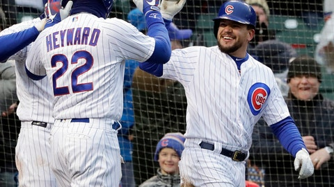 Chicago Cubs' Kyle Schwarber, right, celebrates with Jason Heyward (22) after they scoring on a wild pitch by Atlanta Braves relief pitcher Peter Moylan during the eighth inning of a baseball game Saturday, April 14, 2018, in Chicago. (AP Photo/Nam Y. Huh)