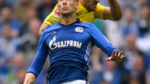 Schalke's Leon Goretzka and Dortmund's Sokratis challenge for the ball during the German Bundesliga soccer match between FC Schalke 04 and Borussia Dortmund in Gelsenkirchen, Germany, Sunday, April 15, 2018. (AP Photo/Martin Meissner)