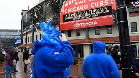 Fans do their best to stay warm and dry outside Wrigley Field after a baseball game between the Atlanta Braves and the Chicago Cubs was postponed on Sunday, April 15, 2018, in Chicago. The game is rescheduled for Monday, May 14, 2018. (AP Photo/Matt Marton)