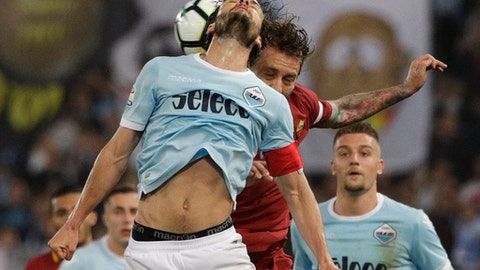 Lazio's Marco Parolo, front, and Roma's Daniele De Rossi vie for the ball during an Italian Serie A soccer match between AS Roma and Lazio, at the Olympic stadium in Rome, Sunday, April 15, 2018. (AP Photo/Gregorio Borgia)