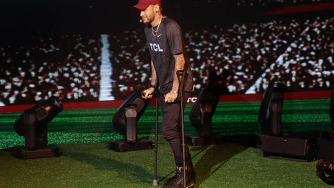 Brazil's soccer star Neymar walks on crutches during a promotional event from one of his sponsors, in Sao Paulo, Brazil, Tuesday, April 17, 2018. The Paris Saint-Germain striker had been found to have suffered a sprain of the right ankle and fissure of the fifth metatarsal after a tangle with Marseille player, Bouna Sarr during a Feb. 25 match. (AP Photo/Andre Penner)