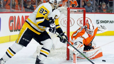 Pittsburgh Penguins' Sidney Crosby, left, tries for a goal as Philadelphia Flyers' Brian Elliott defends during the first period in Game 4 of an NHL first-round hockey playoff series Wednesday, April 18, 2018, in Philadelphia. The Penguins won 5-0. (AP Photo/Tom Mihalek)