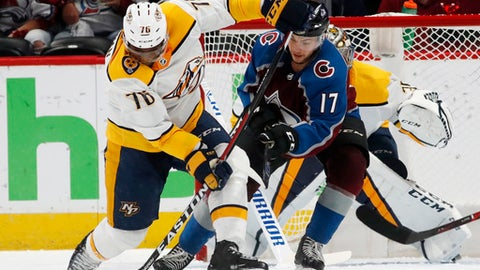 Nashville Predators defenseman P.K. Subban, front, clears the puck after a shot by Colorado Avalanche center Tyson Jost, center, was stopped by Nashville goaltender Pekka Rinne, back, during the second period of Game 4 of an NHL hockey first-round playoff series Wednesday, April 18, 2018, in Denver. (AP Photo/David Zalubowski)