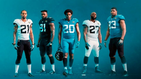 In this image provided by the Jacksonville Jaguars, Jaguars players pose in new team uniforms, to be unveiled Thursday, April 19, 2018, in Jacksonville, Fla. From left are A.J. Bouye (21), Yannick Ngakoue (91), Jalen Ramsey (20), Leonard Fournette (27) and Calais Campbell(93). (Jacksonville Jaguars via AP)