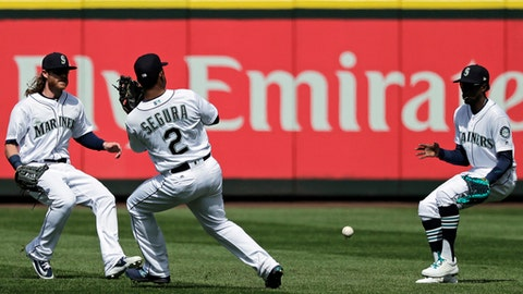 Seattle Mariners center fielder Dee Gordon, right, moves to field a ball hit by Houston Astros' Josh Reddick as Ben Gamel, left, and Jean Segura (2) look on during the fifth inning of a baseball game, Thursday, April 19, 2018, in Seattle. (AP Photo/Ted S. Warren)