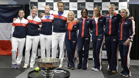 From left, France's Team members Amandine Hesse, Pauline Parmentier, Kristina Mladenovic, captain Yannick Noah and United States' Fed Cup team members, captain Kathy Rinaldi, Sloane Stephens, Madison Keys, Coco Vandeweghe, Bethanie Mattek-Sands, pose for photo after the draw ceremony in Aix-en-Provence, Friday, April 20, 2018. The Fed Cup semifinal matches between France and USA will take place Saturday and next Sunday. (AP Photo/Claude Paris)