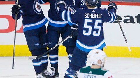 Winnipeg Jets' Andrew Copp (9), Joel Armia (40), Dustin Byfuglien (33) and Mark Scheifele (55) celebrate Armia's goal against the Minnesota Wild during the first period in Game 5 of an NHL hockey first-round playoff series in Winnipeg, Manitoba, Friday, April 20, 2018. (John Woods/The Canadian Press via AP)