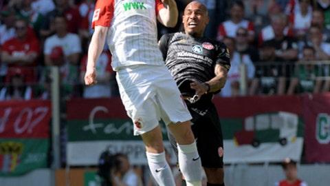 Augsburg's Michael Gregoritsch, left, and Mainz' Nigel de Jong challenge for the ball during the German Bundesliga soccer match between FC Augsburg and FSV Mainz 05, in Augsburg, Germany, Sunday, April 22, 2018. (Stefan Puchner/dpa via AP)