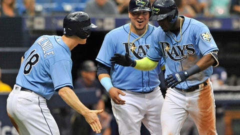Tampa Bay Rays' Joey Wendle (18), Jesus Sucre and Adeiny Hechavarria, right, celebrate at the plate after Hechavarria's three-run home run off Minnesota Twins reliever Alan Busenitz during the sixth inning of a baseball game Sunday, April 22, 2018, in St. Petersburg, Fla. (AP Photo/Steve Nesius)