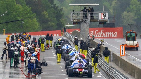 IndyCar drivers sit on pit road as the race is red flagged due to rain during the Honda Indy Grand Prix of Alabama at Barber Motorsports Park, Sunday, April 22, 2018, in Birmingham, Ala. (AP Photo/Butch Dill)