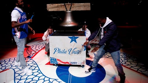Rapper Meek Mills, left, comes out to ring a Liberty Bell replica with actor Kevin Hart, right, before the first half in Game 5 of a first-round NBA basketball playoff series between the Miami Heat and the Philadelphia 76ers, Tuesday, April 24, 2018, in Philadelphia. (AP Photo/Chris Szagola)