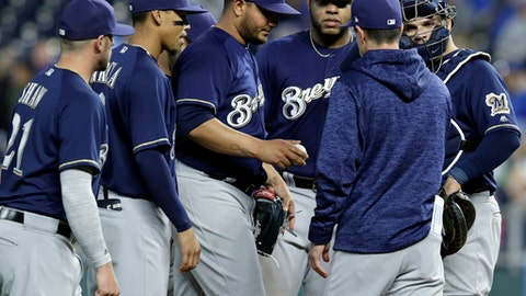 Milwaukee Brewers starting pitcher Jhoulys Chacin hand the ball to Milwaukee Brewers manager Craig Counsell, second from right, during the sixth inning of a baseball game against the Kansas City Royals at Kauffman Stadium in Kansas City, Mo., Wednesday, April 25, 2018. (AP Photo/Orlin Wagner)