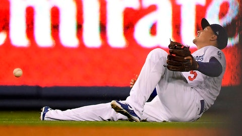 Los Angeles Dodgers shortstop Corey Seager falls as he tries to field a ball hit for a single by Miami Marlins' J.B. Shuck during the ninth inning of a baseball game Wednesday, April 25, 2018, in Los Angeles. (AP Photo/Mark J. Terrill)