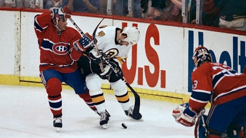 FILE - In this April 27, 1990, file photo, Boston Bruin right wing Dave Christian, back right, tries to block Montreal Canadiens' Mathieu Schneider as they skate for the puck during the first period of Game 5 of an NHL hockey playoff series in Boston. The teams met for seven consecutive seasons in the playoffs. (AP Photo/Peter Southwick, File)