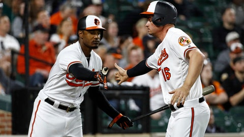Baltimore Orioles' Trey Mancini, right, high-fives teammate Adam Jones after scoring on Manny Machado's single during the third inning of a baseball game against the Tampa Bay Rays, Thursday, April 26, 2018, in Baltimore. (AP Photo/Patrick Semansky)