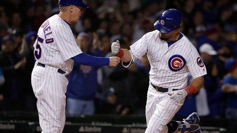 Chicago Cubs' Kyle Schwarber, right, celebrates with third base coach Brian Butterfield after hitting a solo home run against the Milwaukee Brewers during the sixth inning of a baseball game Thursday, April 26, 2018, in Chicago. (AP Photo/Nam Y. Huh)