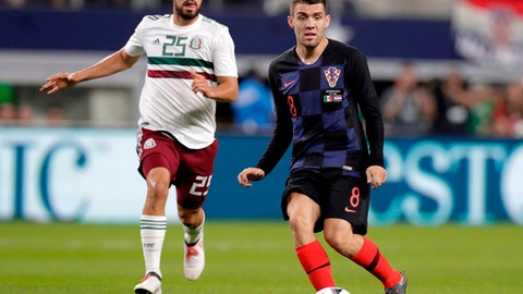FILE - In this photo taken on Tuesday, March 27, 2018, Croatia midfielder Mateo Kovacic makes a pass under pressure from Mexico midfielder Rodolfo Pizarro, left, during a international friendly soccer match in Arlington, Texas. (AP Photo/Tony Gutierrez)