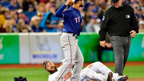 Toronto Blue Jays' Russell Martin sits on third base after being called out during the second inning of the team's baseball game against the Texas Rangers in Toronto, Friday, April 27, 2018. After review, Martin was ruled safe. (Frank Gunn/The Canadian Press via AP)