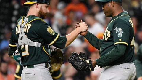 Oakland Athletics relief pitcher Santiago Casilla, right, and catcher Jonathan Lucroy clasp hands after the team's 8-1 win over the Houston Astros in a baseball game Friday, April 27, 2018, in Houston. (AP Photo/Eric Christian Smith)