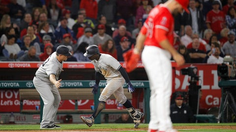 New York Yankees' Didi Gregorius, center, is congratulated by third base coach Phil Nevin after hitting a home run off Los Angeles Angels relief pitcher Blake Parker, foreground, during the 10th inning of a baseball game Friday, April 27, 2018, in Anaheim, Calif. The Yankees won 4-3. (AP Photo/Jae C. Hong)