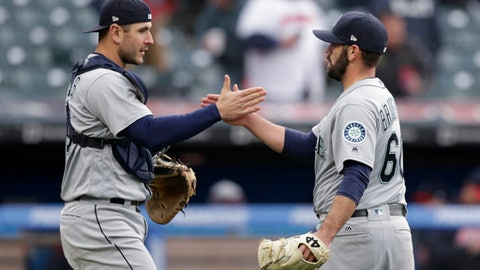 Seattle Mariners relief pitcher Chasen Bradford, right, and catcher David Freitas celebrate after the Mariners defeated the Cleveland Indians 12-4 in a baseball game Saturday, April 28, 2018, in Cleveland. (AP Photo/Tony Dejak)