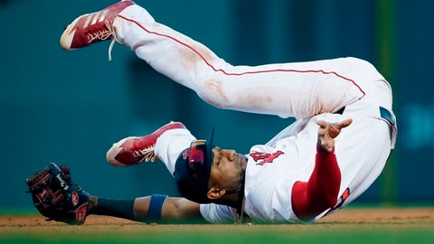 Boston Red Sox's Eduardo Nunez falls on his back while fielding the cut off throw on an RBI double by Tampa Bay Rays' Jesus Sucre during the eighth inning of a baseball game in Boston, Saturday, April 28, 2018. (AP Photo/Michael Dwyer)