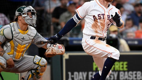 Houston Astros' Derek Fisher, right, watches his two-run home run off Oakland Athletics relief pitcher Daniel Coulombe during the fourth inning of a baseball game, Saturday, April 28, 2018, in Houston. (AP Photo/Eric Christian Smith)