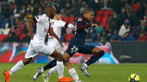 PSG's Kylian Mbappe, right, duels for the ball with Guingamp's Jeremy Sorbon, left, and Nicolas Benezet during the French League One soccer match between Paris Saint Germain and Guingamp at the Parc des Princes stadium in Paris, Sunday, April 29, 2018. (AP Photo/Thibault Camus)