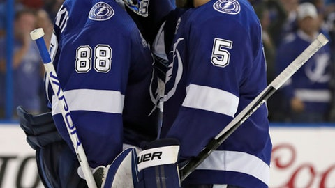 Tampa Bay Lightning goaltender Andrei Vasilevskiy (88) celebrates with defenseman Dan Girardi (5) after the Lightning defeated the Boston Bruins 4-2 during Game 2 of an NHL second-round hockey playoff series Monday, April 30, 2018, in Tampa, Fla. (AP Photo/Chris O'Meara)