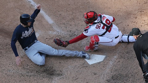 Apr 11, 2018; Washington, DC, USA; Atlanta Braves first baseman Freddie Freeman (5) slides into home plate ahead of the tag of Washington Nationals catcher Pedro Severino (29) to score a run in the twelfth inning at Nationals Park. The Braves won 5-3 in twelve innings. Mandatory Credit: Geoff Burke-USA TODAY Sports