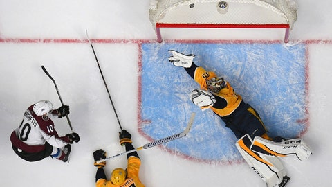 Apr 20, 2018; Nashville, TN, USA; Colorado Avalanche right wing Sven Andrighetto (10) scores the winning goal past a diving Nashville Predators goalie Pekka Rinne (35) and Nashville Predators left wing Scott Hartnell (17) during the third period in game five of the first round of the 2018 Stanley Cup Playoffs at Bridgestone Arena. Mandatory Credit: Christopher Hanewinckel-USA TODAY Sports