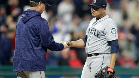 Seattle Mariners starting pitcher Erasmo Ramirez, right, hands the ball to manager Scott Servais during the sixth inning of the team's baseball game against the Cleveland Indians, Friday, April 27, 2018, in Cleveland. (AP Photo/Tony Dejak)
