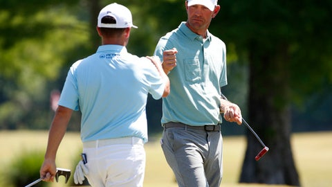 Chez Reavie, left, talks with teammate Lucas Glover on the first green during the final round of the PGA Zurich Classic golf tournament's two-man team format at TPC Louisiana in Avondale, La., Sunday, April 29, 2018. (AP Photo/Tyler Kaufman)
