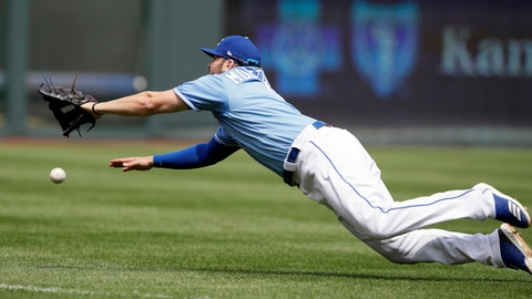 Kansas City Royals third baseman Mike Moustakas dives for a fly ball hit by Chicago White Sox' Nicky Delmonico (30) during the fourth inning of a baseball game at Kauffman Stadium in Kansas City, Mo., Sunday, April 29, 2018. Delmonico doubled on the play. (AP Photo/Orlin Wagner)