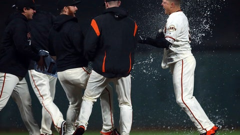 San Francisco Giants' Nick Hundley, right, celebrates after making the game-winning hit against the San Diego Padres in the ninth inning of a baseball game Monday, April 30, 2018, in San Francisco. The Giants won 6-5. (AP Photo/Ben Margot)