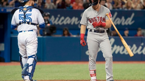 FILE - In this April 24, 2018, file photo, Boston Red Sox's Andrew Benintendi strikes out during the eighth inning for his fourth strikeout of the night, as Toronto Blue Jays catcher Russell Martin walks away during a baseball game in Toronto. There were more strikeouts than hits in the first month of the season, when home runs dipped from last year's record during a cold and wet April. (Fred Thornhill/The Canadian Press via AP, File)