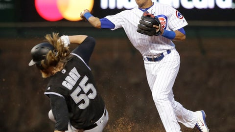 Chicago Cubs' Addison Russell, right, turns the double play, throwing to first after forcing out Colorado Rockies' Jon Gray (55) at second, to get Charlie Blackmon at first during the third inning of a baseball game Tuesday, May 1, 2018, in Chicago. (AP Photo/Charles Rex Arbogast)