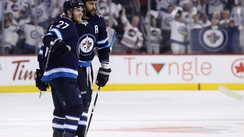 Winnipeg Jets' Nikolaj Ehlers (27) and Dustin Byfuglien (33) celebrating after Byfuglien scored against the Nashville Predators during second period NHL hockey playoff action in Winnipeg, Manitoba, Tuesday May 1, 2018. (Trevor Hagan/The Canadian Press via AP)