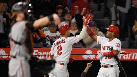 Los Angeles Angels' Andrelton Simmons, left, is congratulated by Luis Valbuena, right, after Simmons scored from second on a throwing error by Baltimore Orioles shortstop Manny Machado as catcher Chance Sisco throws out a new ball during the sixth inning of a baseball game Tuesday, May 1, 2018, in Anaheim, Calif. (AP Photo/Mark J. Terrill)
